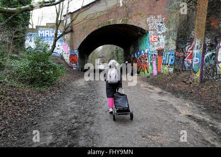 Rear view of senior woman & cart trolley walking on parkland walk path near railway bridge Crouch End, London N4 - Stock Photo