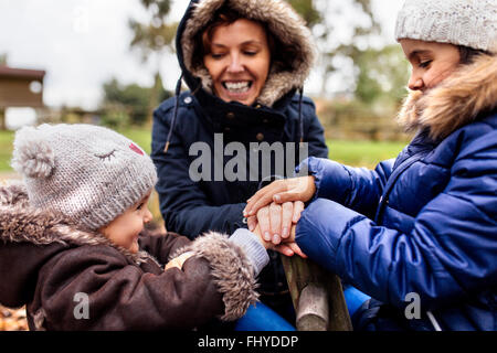 Two little sisters with her mother on a playground in autumn - Stock Photo