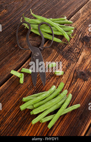 Raw fresh green beans with water drops on brown wooden textured table. Fresh vegetable eating. - Stock Photo