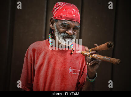 Portrait of an elderly Cuban man in a red shirt with a cigars in his hand - Stock Photo