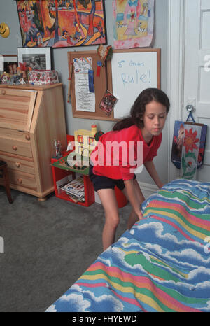 10 year old 5th grader in her bedroom makes her bed at home in Brooklyn, NY. - Stock Photo