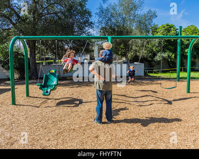 Four young kids having fun on a giant swing set that an adult female is swinging them on in Libbey Park, Ojai, California. - Stock Photo