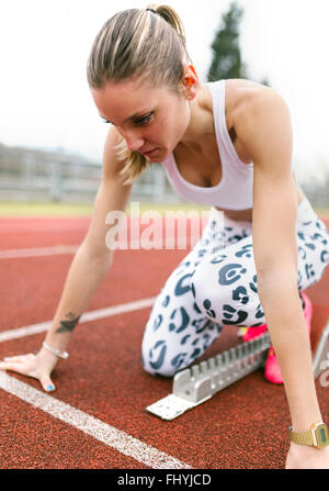 Athlete woman on a running track - Stock Photo