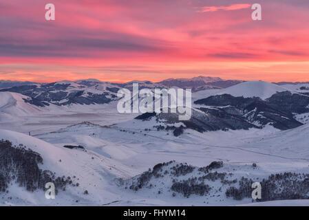 Italy, Umbria, Monti Sibillini National Park, Sunset on plateau Piano Grande of Castelluccio di Norcia  in Winter - Stock Photo