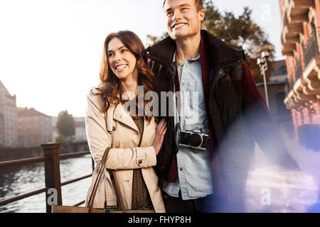 Germany, Berlin, happy young couple walking along River Spree - Stock Photo