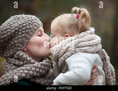 Young woman kissing her little daughter in autumn - Stock Photo