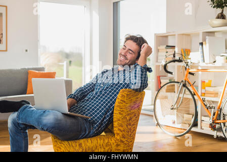 Portrait of smiling young man sitting on armchair in the living room with laptop - Stock Photo