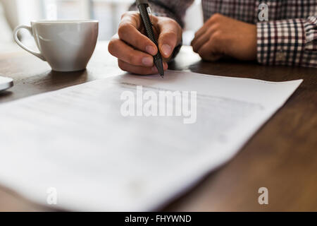 Close-up of man signing document on table - Stock Photo