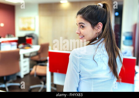 Smiling young businesswoman looking over her shoulder in an office - Stock Photo