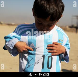 Kabul, Afghanistan. 26th Feb, 2016. Afghan boy Murtaza Ahmadi shows his new jersey signed by Argentina soccer star - Stock Photo