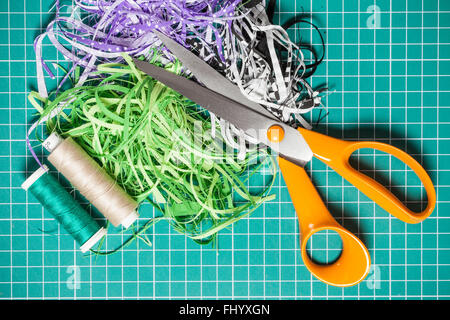 Textile offcuts, threads and scissors on checkered rotary cut mat - Stock Photo