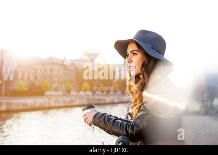 Germany, Berlin, young woman with coffee to go at River Spree - Stock Photo