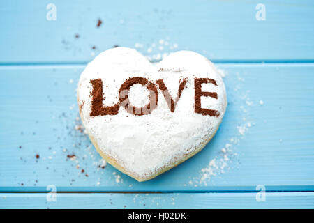 Pastry with the word 'Love' on light blue wood - Stock Photo