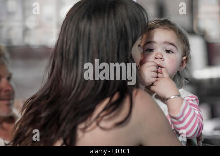 Portrait of baby girl with finger in mouth on the arms of her mother - Stock Photo