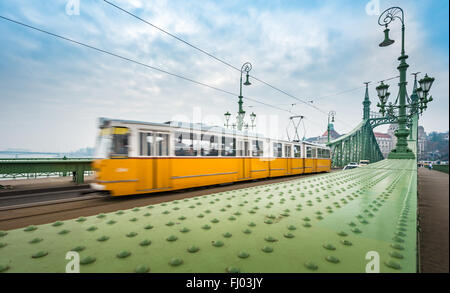 Wide view on yellow Tram crossing Liberty bridge in Budapest, Hungary, Europe. Major landmark and tourist attraction. - Stock Photo