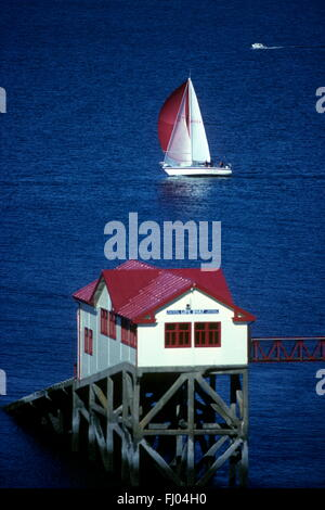 Red sails of a passing yacht and the red roof of the old lifeboat station at Mumbles, voted best place to live in - Stock Photo