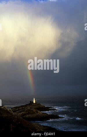 There's light at the end of the Rainbow. A rainbow falls from the clouds in a shaft of light at Mumbles Light house,Swansea - Stock Photo