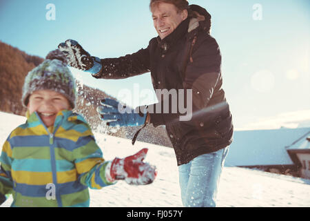Italy, Val Venosta, Slingia, father and son having a snowball fight - Stock Photo