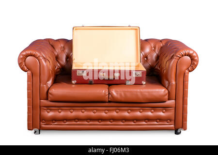 Old leather couch with an open empty vintage suitcase isolated on white with clipping path - Stock Photo