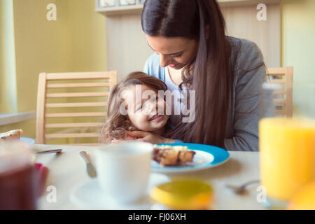 Portrait of smiling little girl and her mother at breakfast table - Stock Photo