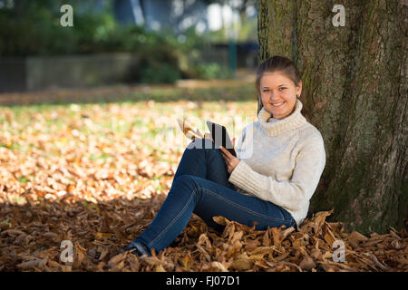 Pretty woman reading ebook sitting near the hearth stock photo woman using tablet young woman in autumn park sitting near tree reading ebook stock photo fandeluxe Ebook collections