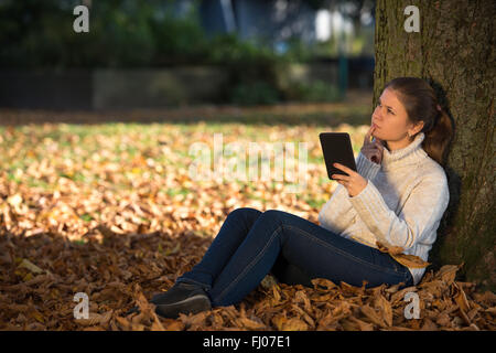 Pretty woman reading ebook sitting near the hearth stock photo young woman in autumn park sitting near tree reading ebook stock photo fandeluxe Ebook collections