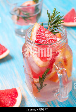 lemonade with grapefruit and rosemary in a mason jar on a blue background - Stock Photo