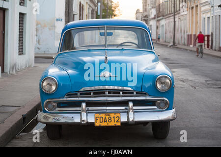 Daily life in Cuba - old Plymouth blue car parked in street at Cienfuegos, Cuba, West Indies, Caribbean, Central - Stock Photo