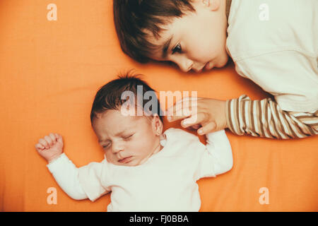 Newborn baby girl and brother lying on bed - Stock Photo