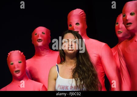 Tina Keserovic in her role as Beate Zschaepe performs surrounded by extras wearing pink body suits during the photo - Stock Photo