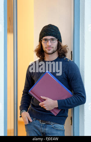 Portrait of young man wearing spectacles and woolly hat holding file - Stock Photo