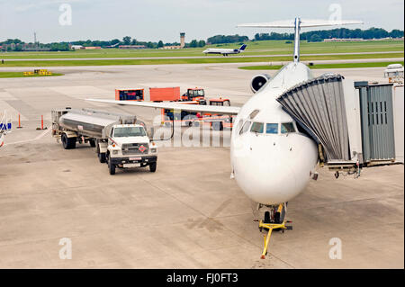 Airliner Being Serviced Between Flights While Another Lands - Stock Photo