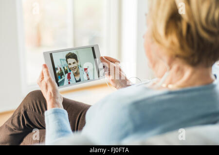 Senior woman looking at picture of young man on digital tablet - Stock Photo