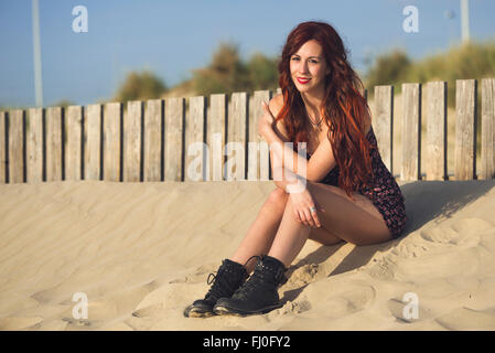 Spain, Cadiz, portrait of young redheaded woman sitting on the beach - Stock Photo