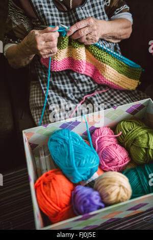 Box of different balls of wool and knitting senior woman - Stock Photo