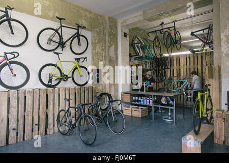 Mechanics working in a custom-made bicycle store - Stock Photo