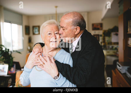 Senior couple hugging and kissing at home - Stock Photo