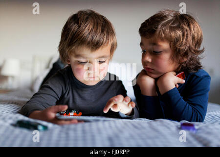 Two little boys lying on bed playing with digital tablet - Stock Photo
