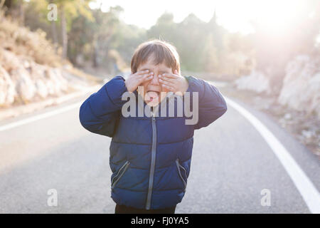 Spain, Siurana, screaming little boy standing on lane of empty country road covering eyes with his hands - Stock Photo