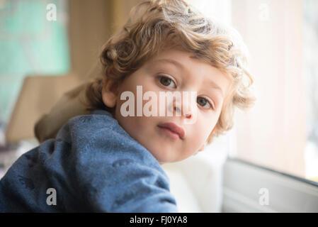 Portrait of little boy looking over his shoulder - Stock Photo