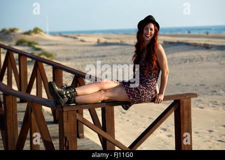 Spain, Cadiz, portrait of young redheaded woman sitting on railing of boardwalk at the beach - Stock Photo