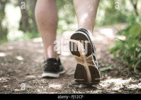Close-up of feet of man running in forest - Stock Photo