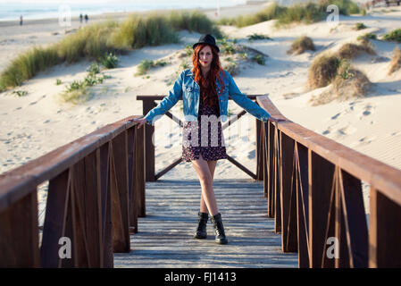 Spain, Cadiz, portrait of young redheaded woman standing on boardwalk at the beach - Stock Photo