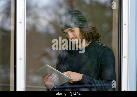 Young man standing behind window using digital tablet - Stock Photo