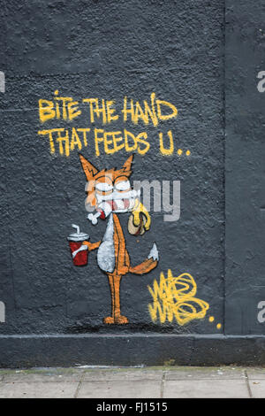 Bite the Hand that Feeds you Graffiti on the side of a building in Stokes Croft, Bristol - Stock Photo