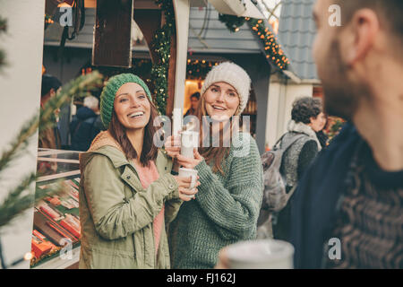 Happy friends having a hot punch on the Christmas Market - Stock Photo