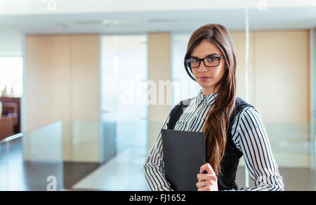 Portrait of young woman with black file in an office - Stock Photo