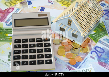Pocket calculator with blank display. Model of a New building. In the background many euro banknotes and coins - Stock Photo