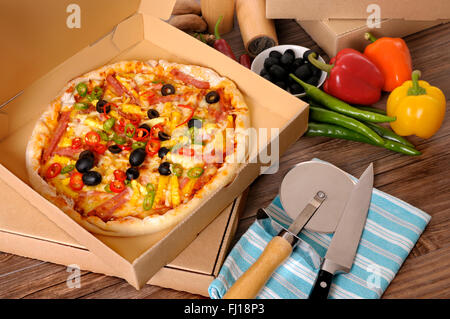Freshly baked Pizza in a delivery box surrounded by various ingredients on a wood table or worktop. - Stock Photo