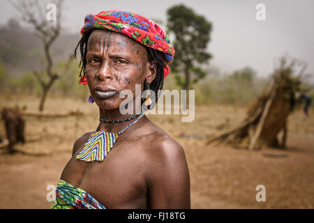Portrait of a Mbororo woman with scars on her face and decorative necklace outside her hut. - Stock Photo